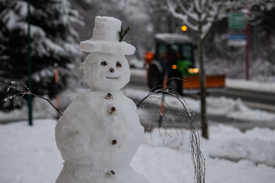 Ein Schneemann steht in Schellerhau im sächsischen Osterzgebirge am Straßenrand währen der Winterdienst im Hintergrund vorbei fährt.