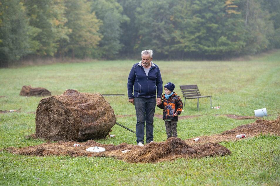 Bauer Christian Junghanns und sein Enkel Finn stehen auf der Wiese am Birkenhainer Weg, wo Jugendliche randaliert haben.