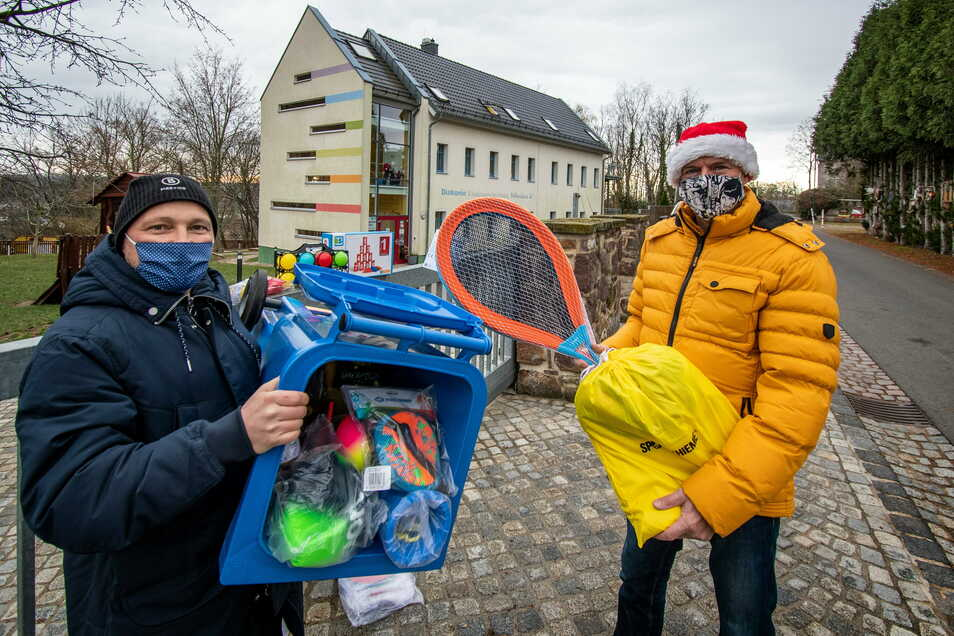 Renè Vettermann (links) und Jörg Lippert vom VfB Leisnig haben die Mädchen und Jungen der Kita Nikolaus in Polditz mit einer Tonne voll Spielzeug überrascht. Die wurde aufgrund der Corona-Regeln vor der Tür abgestellt.