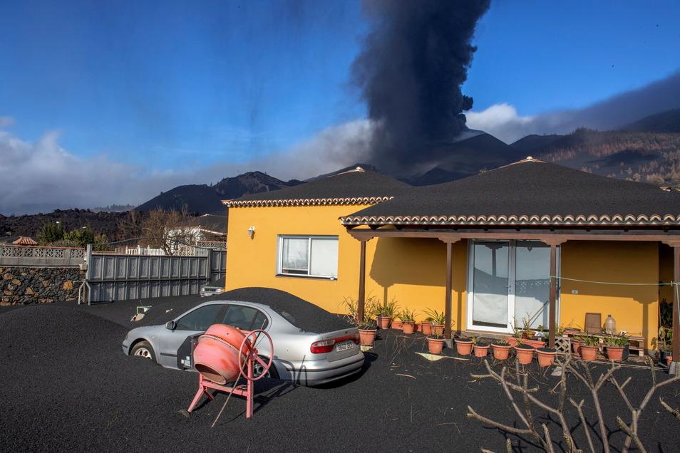 Haus und Wagen stehen unter Asche, während der Vulkan im Hintergrund weiter Aschenwolken und Lava ausstösst.
