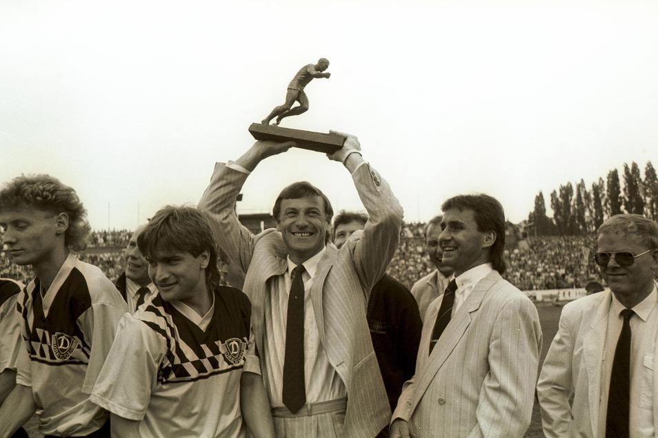 Es ist vollbracht! Nach zehn Jahren hat Dynamo Dresden die Herrschaft des Vornamensvetters aus Berlin, des BFC, gebrochen. Eduard Geyer hat die Schwarz-Gelben zum DDR-Meistertitel 1988/89 geführt. Stolz hält er den Siegerpokal nach oben; die Spieler Uwe J