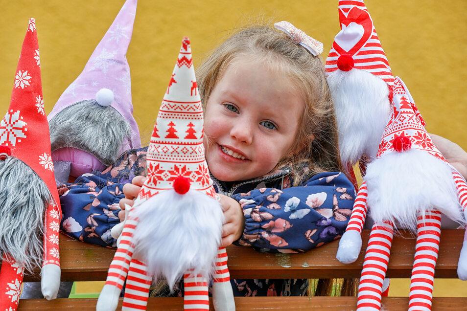 Die vierjährige Mia mit den selbst genähten Weihnachtswichteln. Mitstreiter vom Oderwitzer Kulturverein haben sie gefertigt. Sie werden Anfang Dezember an einem Stand verkauft.