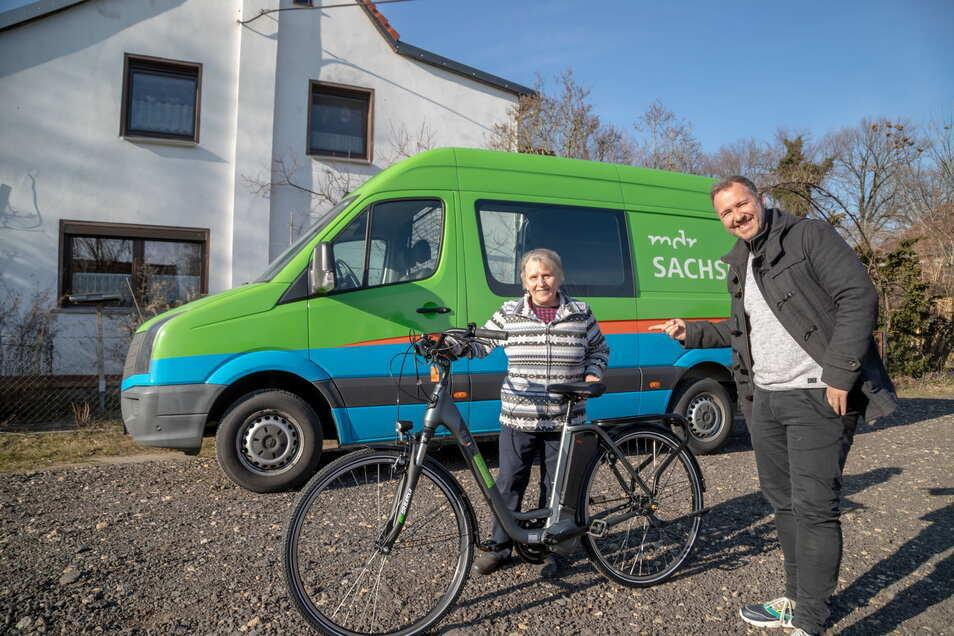 MDR-Moderator Silvio Zschage überbringt ein E-Bike an Renate Schiewart aus Geheege. Sie hat es am Morgen bei Sachsenradio gewonnen.