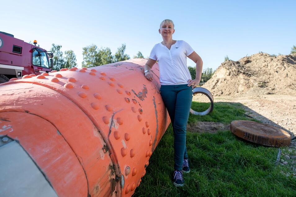 Sabine Neumann vom Förderverein Funkturm Wilsdruff steht vor dem Rest der Riesenantenne, der jetzt zu einem Denkmal werden soll.