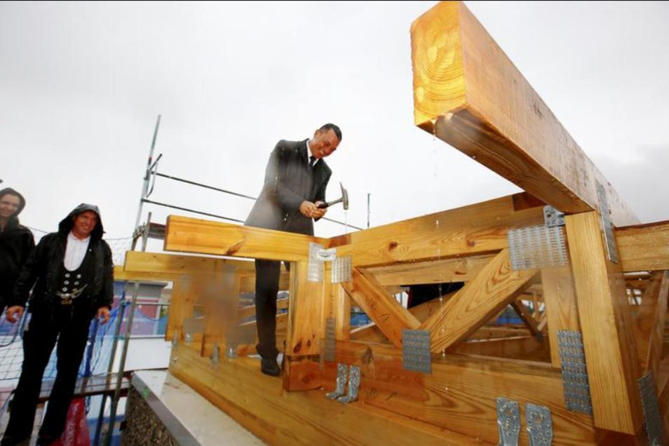 Nicht gerade vergnügungssteuerpflichtig ist das Einschlagen eines Richtnagels im strömenden Regen. Landratsbeigeordneter Udo Witschas bewerkstelligte das am Dienstag in der Kamenzer Saarstraße mit Bravour.