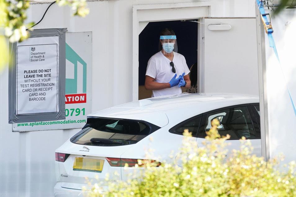 Ein Fahrzeug fährt vor ein Drive-Thru Corona-Testzentrum: In Teilen Englands gelten wieder schärfere Maßnahmen.