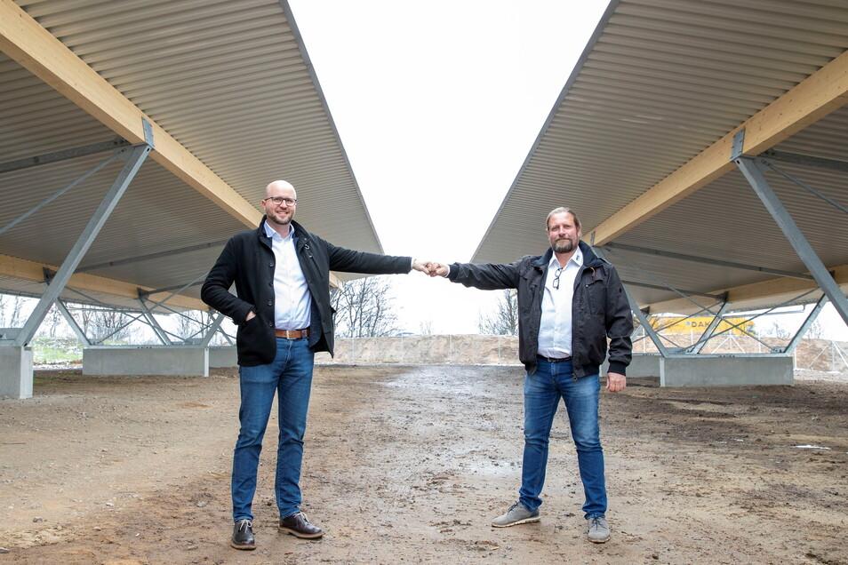Die beiden Geschäftsführer David Riedrich (links) und Torsten Freudenberg stehen auf dem künftigen Parkplatz der Firma. Das Besondere: die Dächer der Carports sind mit Solarzellen bestückt.