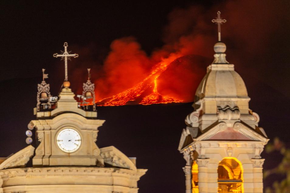 Lava bricht aus einem Krater des Ätna, Europas größtem aktiven Vulkan: Im Vordergrund ist die Kirche Santa Maria della Guardia in Belpasso in der Nähe von Catania zu sehen.