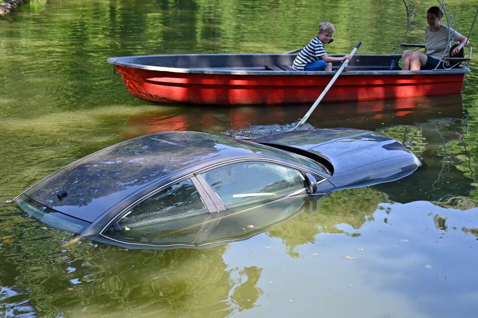 """Ein Auto ist im Wasser des Schlossteiches zu sehen. """"Versinken"""" hat der Schweizer Künstler Roman Signer seine Arbeit im Rahmen der Ausstellung """"Gegenwarten/Presences"""" genannt. Zwischen dem 15. August und 25. Oktober sind die Arbeiten zu sehen."""
