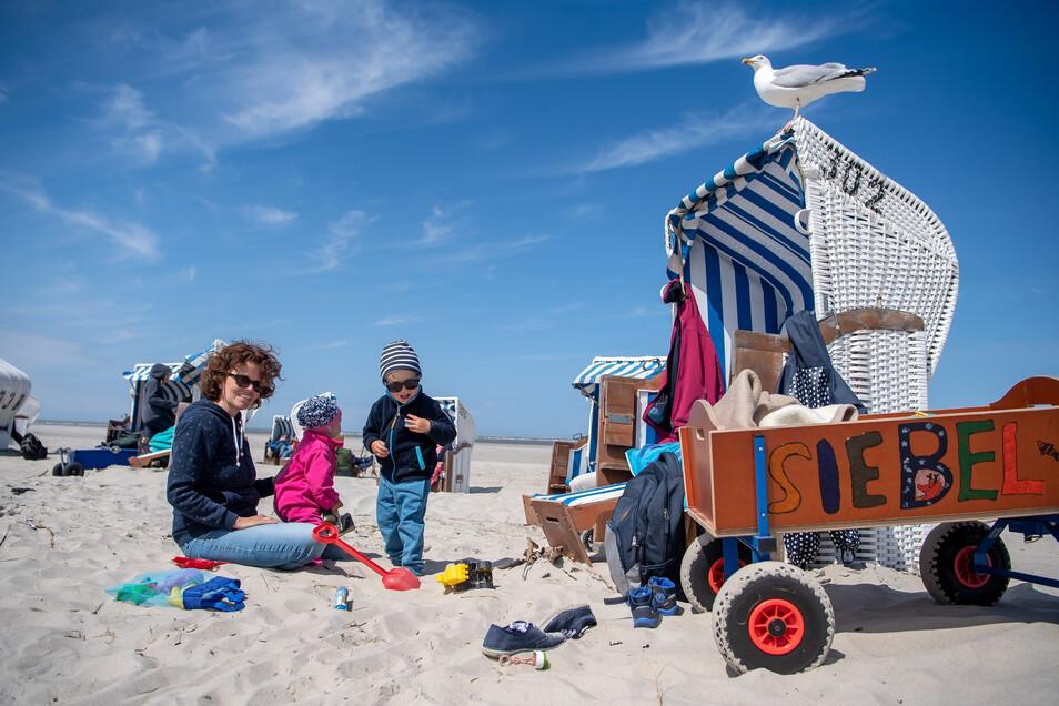 Stephanie aus Köln sitzt mit ihren Kindern am Strand.