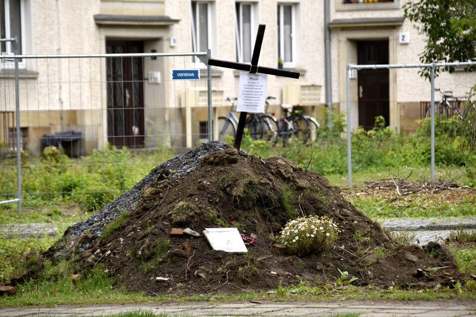 """Ein """"Mahnmal"""" für gefallte Bäume und Sträucher: Mit diesem Erdhügel samt Kreuz äußern Anwohner ihren Protest gegen das Bauvorhaben."""