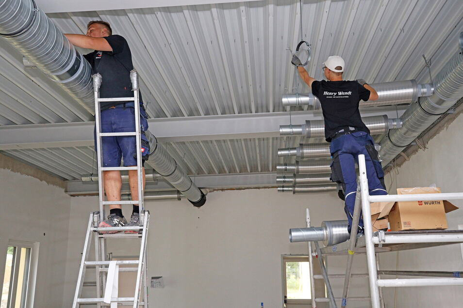 Mitarbeiter der Gröditzer Firma Henry Wendt bauen Lüftungsrohre ein.