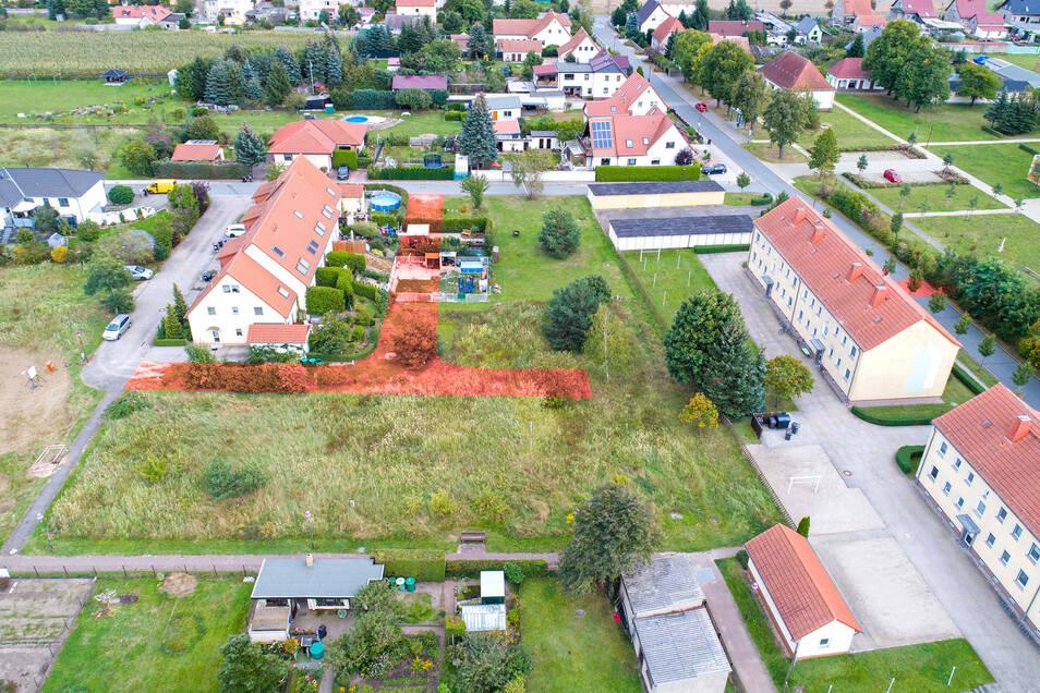 Diese Luftbild-Aufnahme stammt von 2017. Rotbraun eingezeichnet ist die Straße, die eigentlich geplant war. Doch ein paar Bewohner der Reihenhäuser (links) hatten schon damals ihre Grundstücke erweitert.