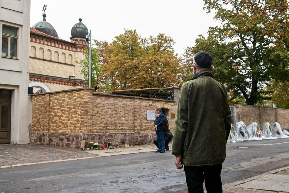 Menschen stehen während einer Schweigeminute zum Gedenken an die Opfer des Terroranschlags von Halle/Saale vor der Synagoge.