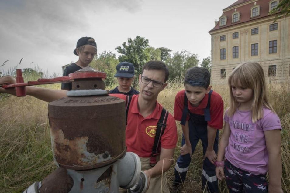 Veit Ludewig zeigt den Hortkindern, wie ein Hydrant funktioniert.