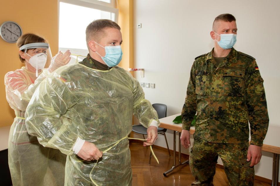 Dem Oberstabsgefreiten der Bundeswehr, Christoph Strogies, wird im Corona-Testzentrum im SkZ Großenhain beim Anlegen der Schutzkleidung geholfen. Drei Bundeswehr-Angehörige sind hier im Einsatz.