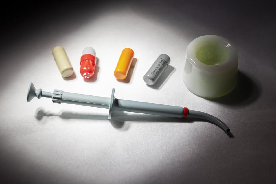 Eine Amalgam-Pistole und Amalgam-Kapseln vor der Verarbeitung zu einer Zahnfüllung.
