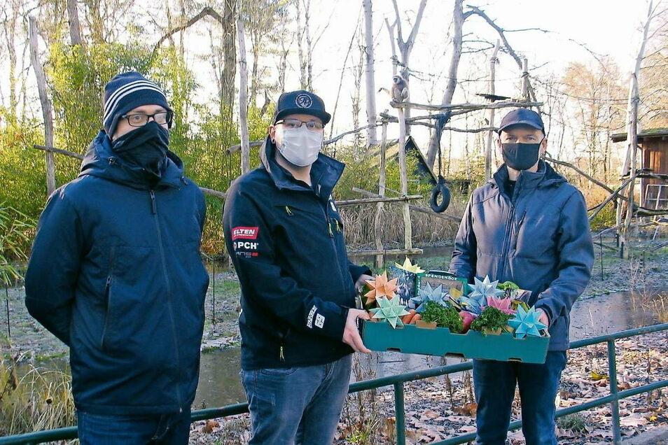 Tobias Jäckel und Florian Fischer bringen Tierparkleiter Gert Emmrich (v.li.) Weihnachtssterne und eine Spende von 1.200 Euro aus ihrer Sterneaktion für den Tierpark.
