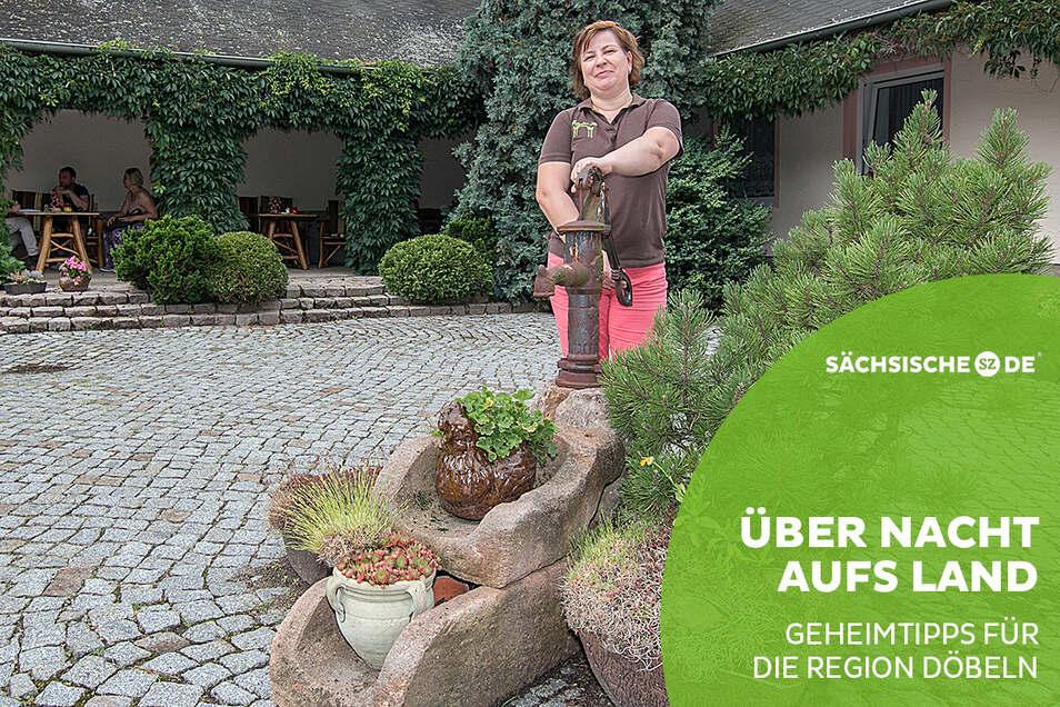 """Heike Möbius steht auf dem schön hergerichteten Innenhof der Pension """"Richzenhainer Hof"""". Seit 1994 können Gäste bei der Wirtin und ihrem Mann Jens am Rande Waldheims übernachten. Nach dem Mauerfall haben beide den Hof nach und nach aufgebaut."""