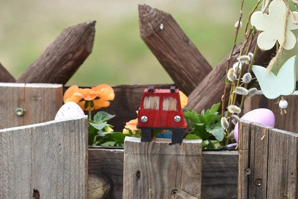 Liebevoll gesägte Details auf den Eigenbau-Blumenkästen am Zaun.