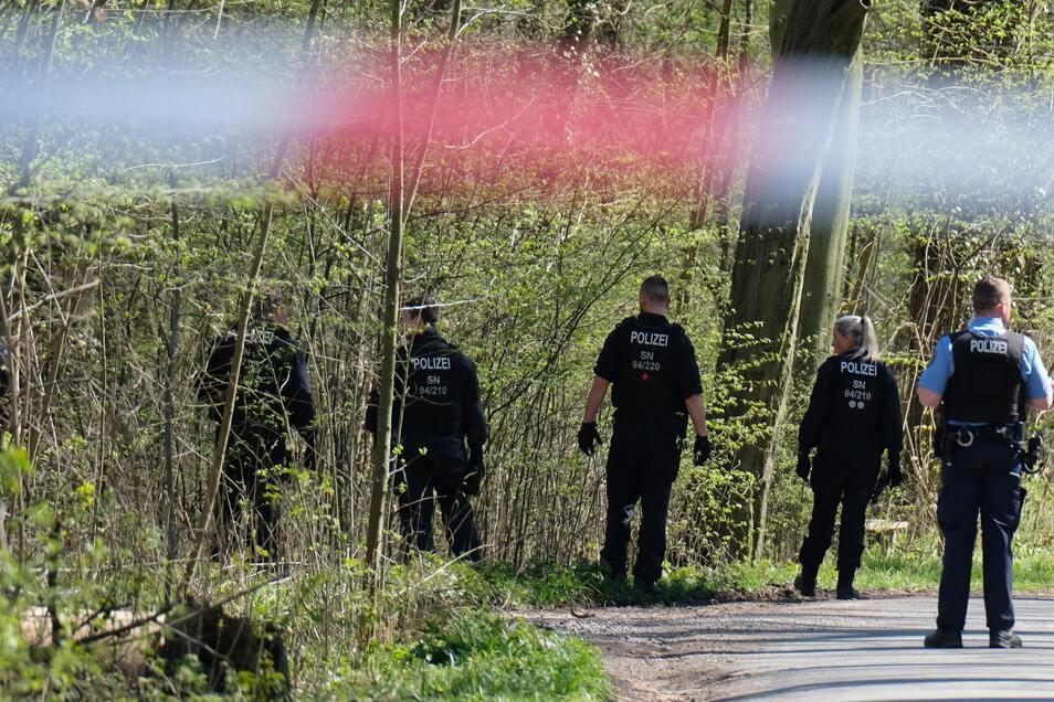 Polizisten suchen im Leipziger Auwald in der Nähe des Tatorts nach Spuren.