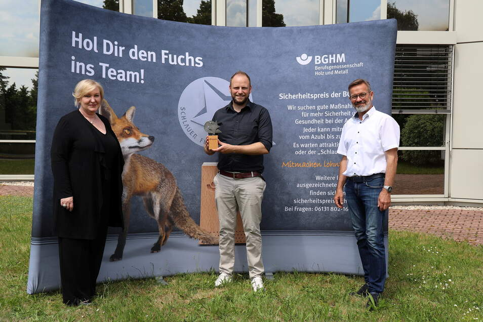"""Ute Emsel und Andreas Brendel von der Berufsgenossenschaft haben Kay Maschke (Mitte) von OKA Büromöbel den """"Schlauen Fuchs"""" überreicht."""