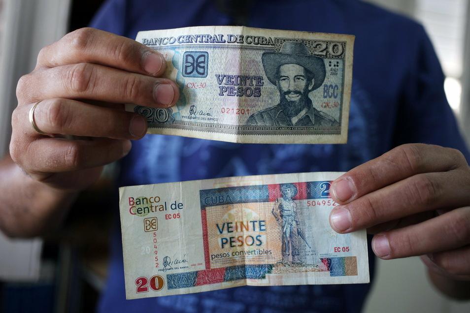Ein Mann zeigt zwei Geldscheine zu je 20 Pesos, einen der offiziellen Landeswährung Peso CUP (oben) und einen von Peso Cubano Convertible CUC (unten). Kuba will zum Beginn des kommenden Jahres eine seiner zwei Währungen abschaffen.
