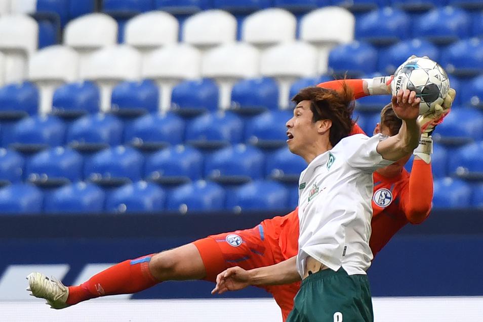 Yuya Osako (l) von Bremen in Aktion gegen Torhüter Alexander Nübel von Schalke.