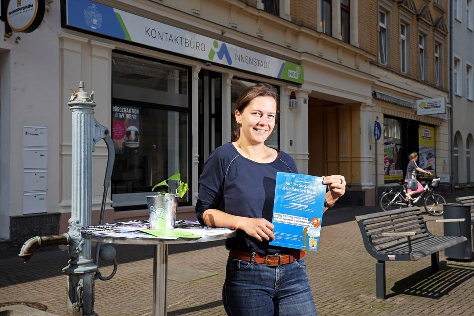 """Anja Dietel zeigt vor ihrem Kontaktbüro die Flyer für die Aktion """"Innenstadtdetektive""""."""