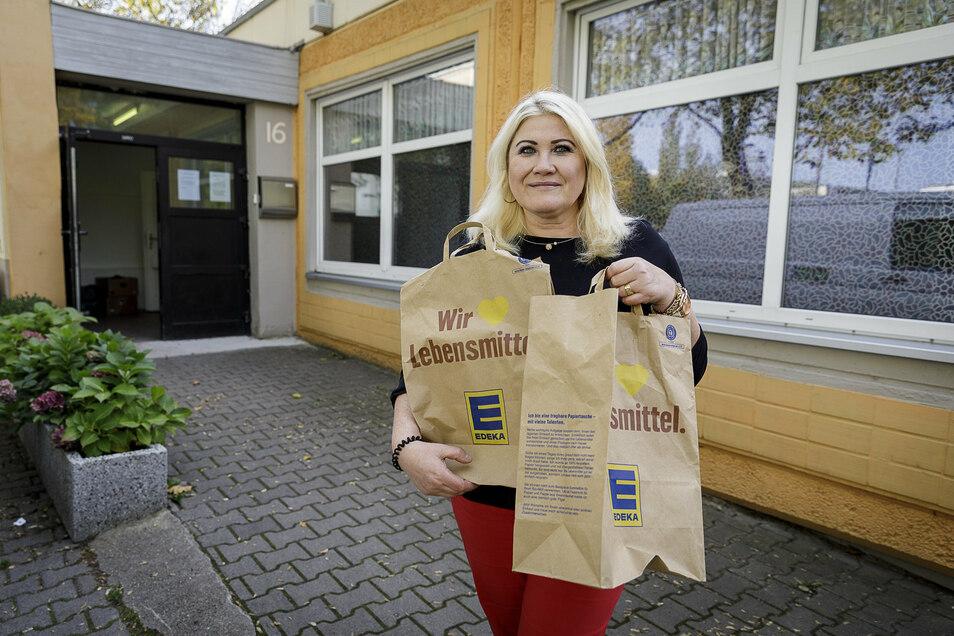 Angelika Baer von der Görlitzer Tafel mit zwei von insgesamt 60 gespendeten Lebensmittel-Tüten von Marktkauf/Edeka.