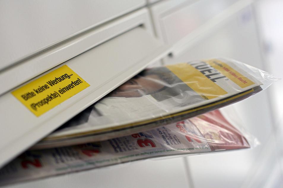 """Eine Gratis-Werbezeitung """"Einkauf Aktuell"""" der Post steckt in einem Briefkasten. Wegen des in Plastik eingeschweißten Werbemagazins  bereitet eine Bürgerinitiative nun Klagen gegen den Konzern vor."""