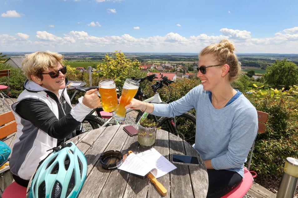 Prost – sich endlich wieder bewirten lassen! Mutter und Tochter machen während einer Radtour Halt in einem Biergarten in Uttenweiler-Offingen in Baden-Württemberg.