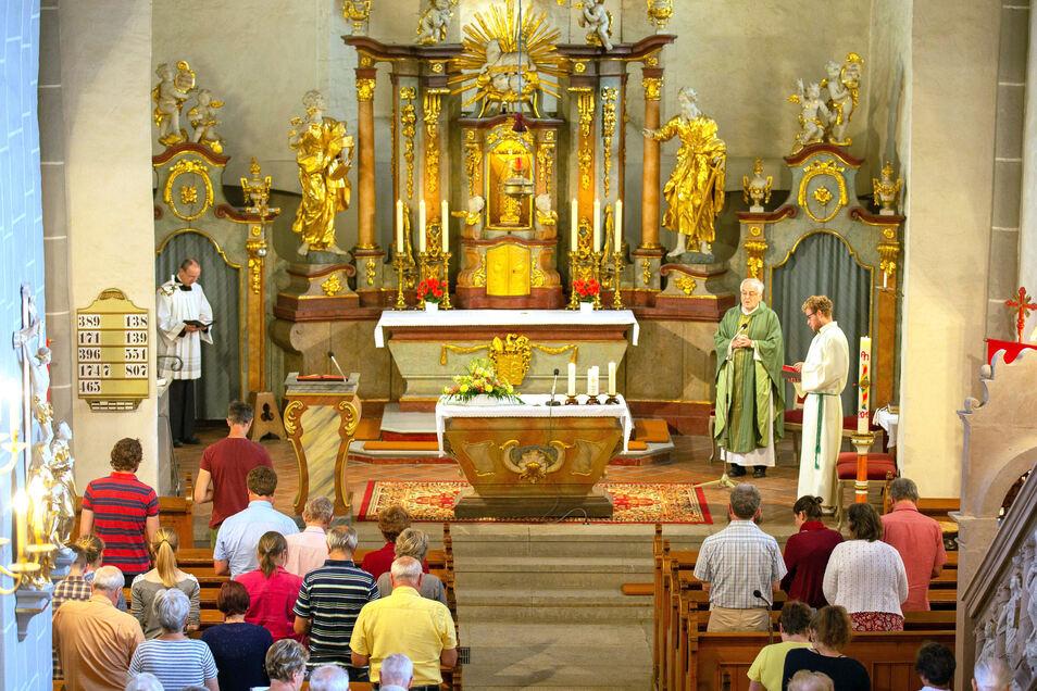 Pfarrer Michael Dittrich (2.v.r.) spricht in der Ostritzer Kirche Mariä Himmelfahrt.