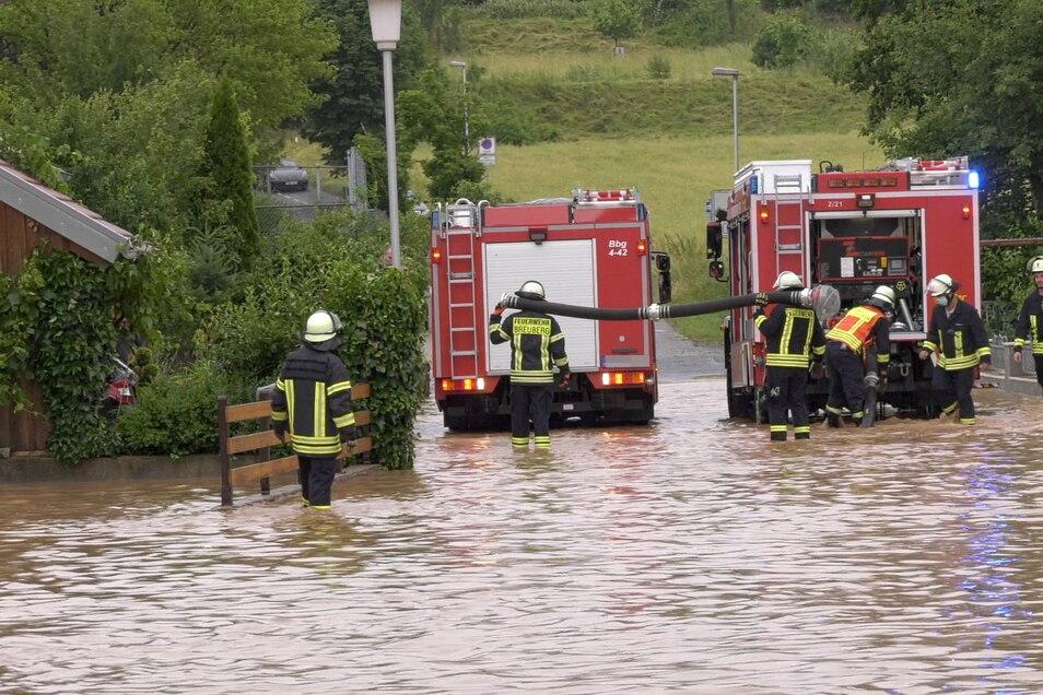 Einsatzkräfte der Feuerwehr stehen auf einer durch ein Unwetter überfluteten Straße in Breuberg im Odenwald.