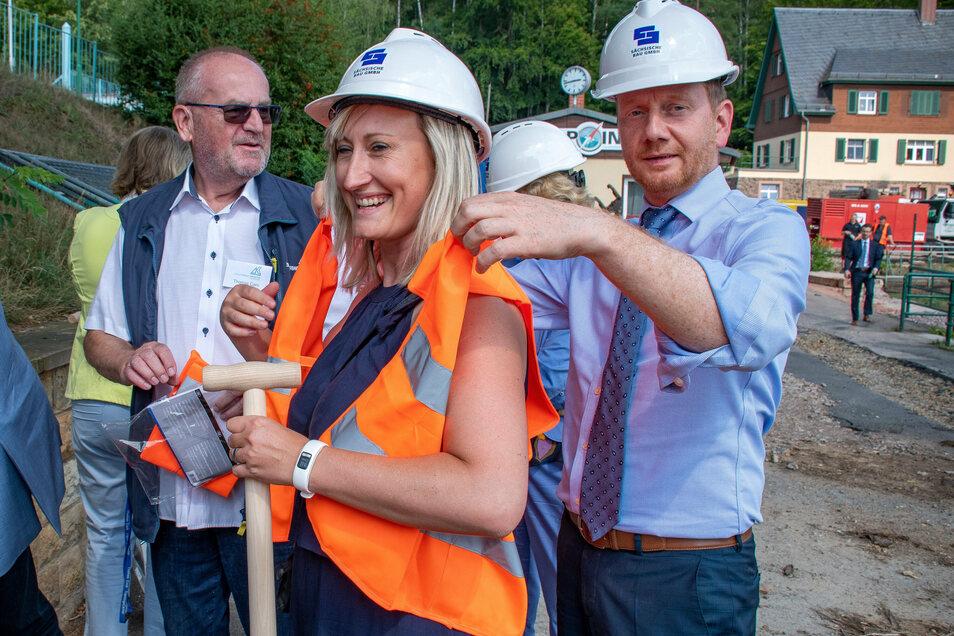 Vor dem Spatenstich hilft Sachsens Ministerpräsident Michael Kretschmer Kriebsteins Bürgermeisterin Maria Euchler in die Warnweste.