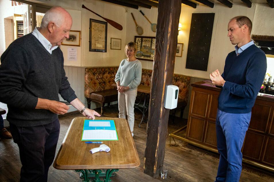 """Prinz William (r.), unterhält sich in Norfolk mit den Wirten des Pubs """"The Rose and Crown"""" Anthony und Jeannette Goodrich über die neuen Regeln für die Wiedereröffnung des Lokals."""