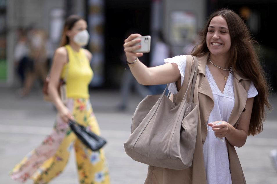 Eine Frau macht ein Selfie ohne Maske, eine andere geht mit Maske vorbei. Nach einer neuen Studie schützt das Tragen einer Maske tatsächlich vor einer Corona-Infektion. Die Inzidenz im Landkreis Meißen liegt am Montag unverändert bei 0,4.