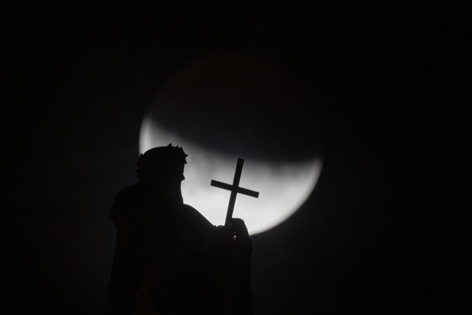 Der Mond ist während einer partiellen Mondfinsternis hinter einer der Mattielli-Statuen auf der Katholischen Hofkirche in Dresden zu sehen.