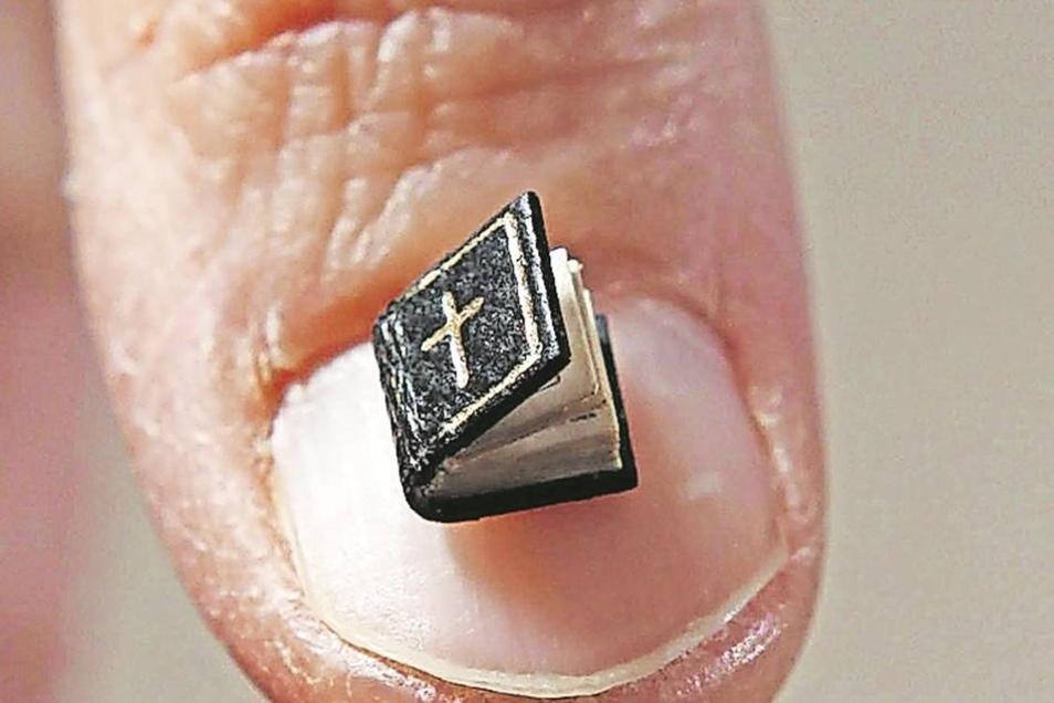 Miniaturausgabe im Bibel-Design: In dem fünf mal fünf Millimeter großen Büchlein steht das Vaterunser abgedruckt.