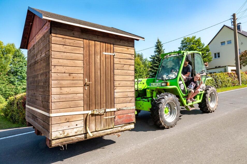 Marcus Roscher hat die Spielzeughütte auf seinen Radlader geladen. Eingewiesen von Stefan Nollau (nicht im Bild) und Tochter Marie bringt er die Hütte zum neuen Bestimmungsort.