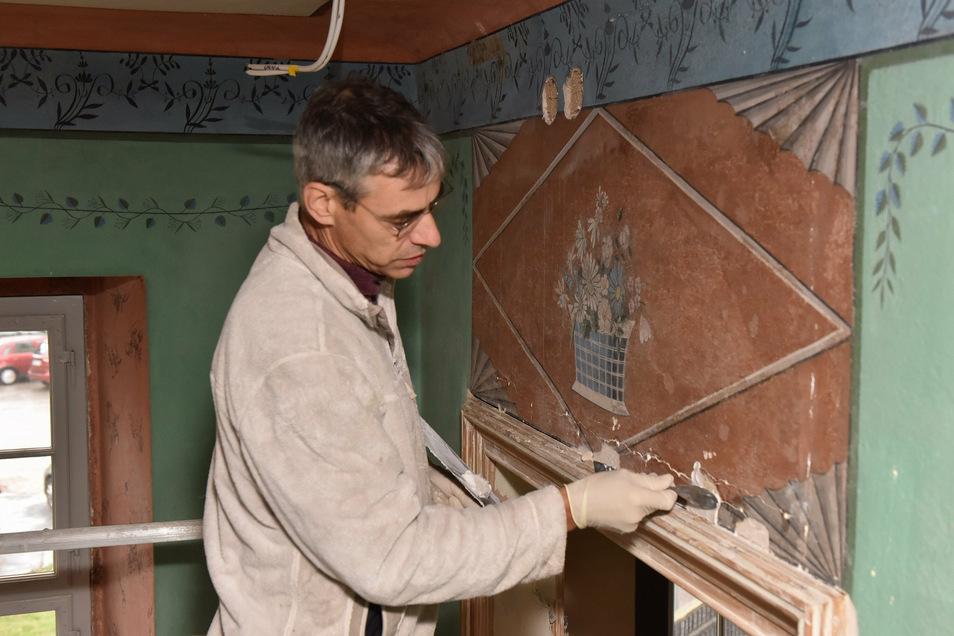 Kirchenmaler Lutz Senninger bereitet im Haupthaus den Untergrund vor, um die historischen Wandmalereien zu restaurieren.