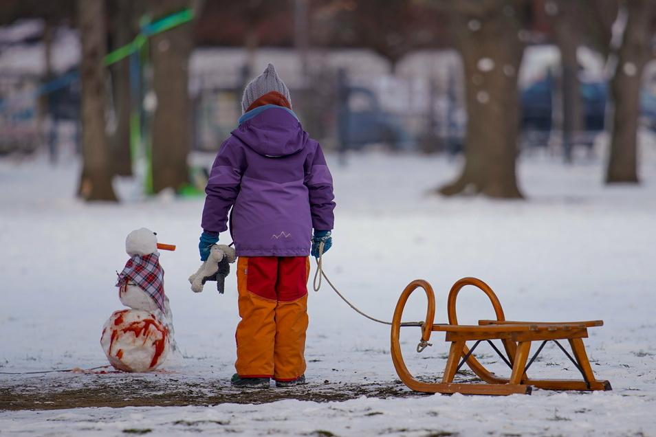 Kind mit Schlitten und Schneemann im Alaunpark.