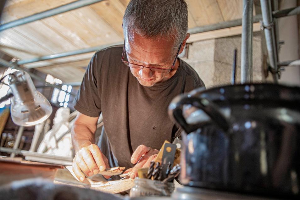 Holzbildhauer Thomas Fauck wurde für die Arbeiten hinzugezogen, er klebt hier gerade Schmuckelemente der Kanzel mit erwärmtem Knochenleim an.