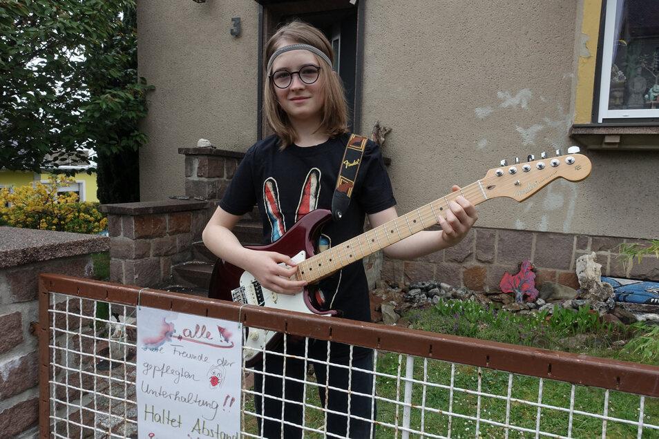 """Till Niemann (12) spielt jeden Abend vor dem Eigenheim seiner Eltern auf dem Geyersberg auf der Elektrogitarre für die Nachbarn. """"Liebe Freunde gepflegter Unterhaltung. Haltet Abstand!"""" steht auf dem Plakat am Gartenzaun."""