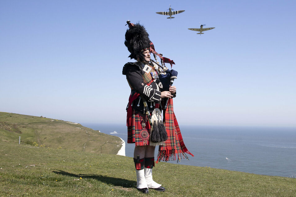 Major Andy Reid von der Scots Guards spielt auf einem Dudelsack auf den Klippen von Dover, während zwei Spitfires, Tiefdecker die vor allem während des Zweiten Weltkrieges von der Royal Air Force und von alliierten Luftstreitkräften eingesetzt wurden, am