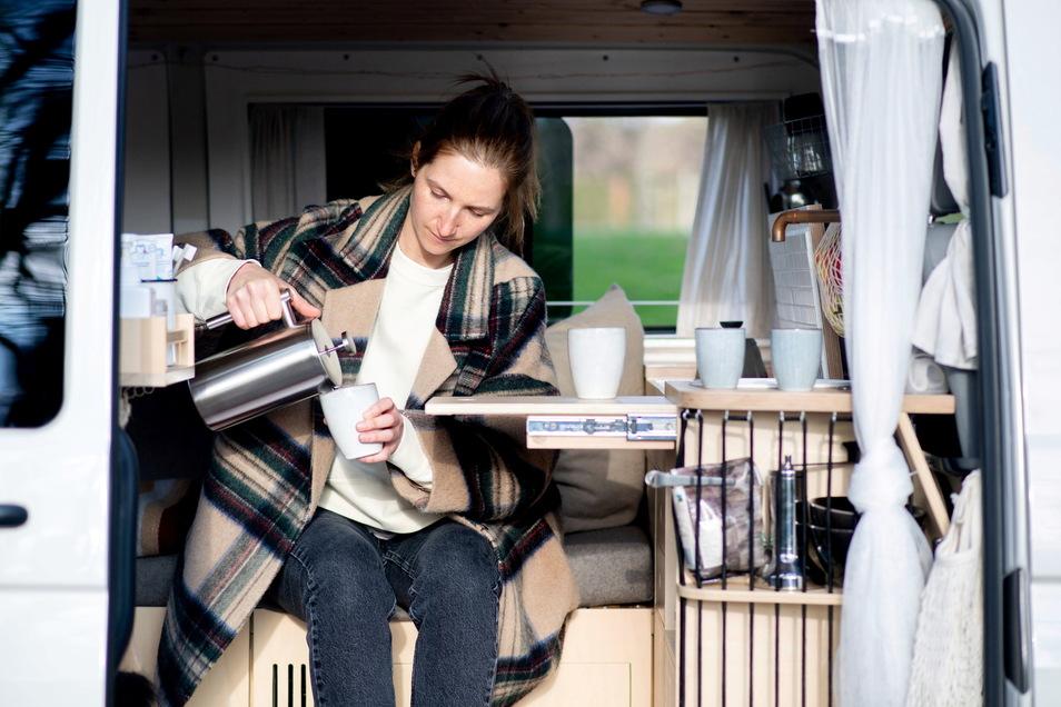 Ines Spicker gießt Kaffee in einen Becher in ihrem Volkswagen T5.