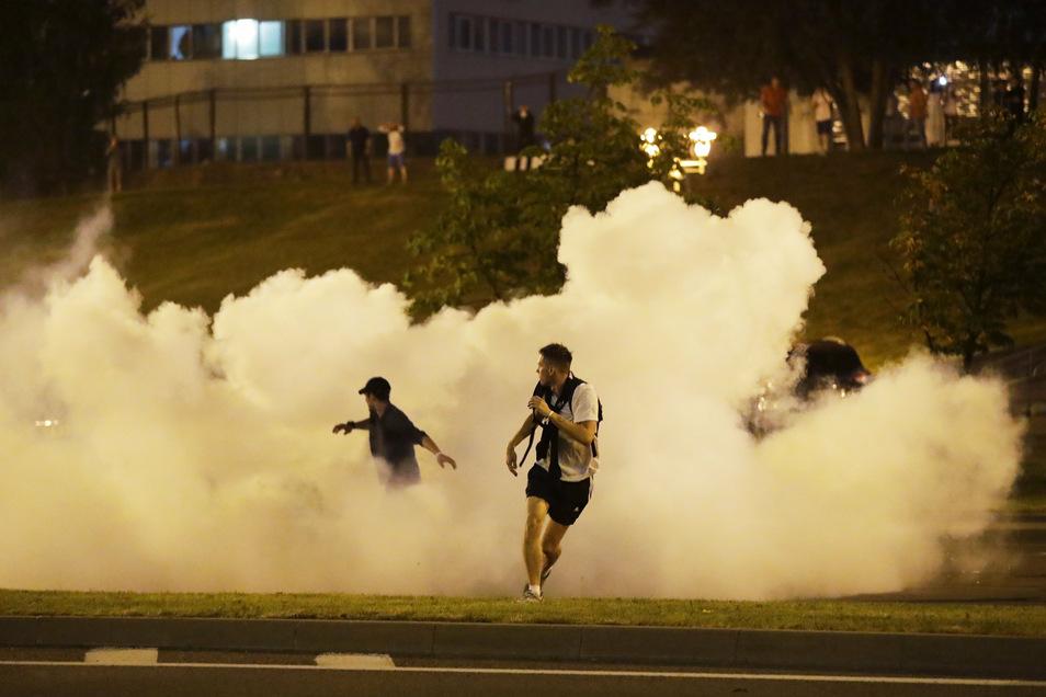 Demonstranten rennen während eines Protests durch Rauch.