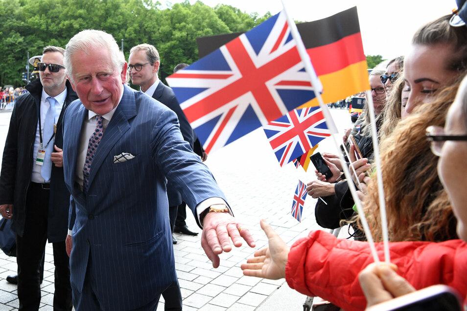 Prinz Charles (vorne) spricht mit Zuschauern vor dem Brandenburger Tor.