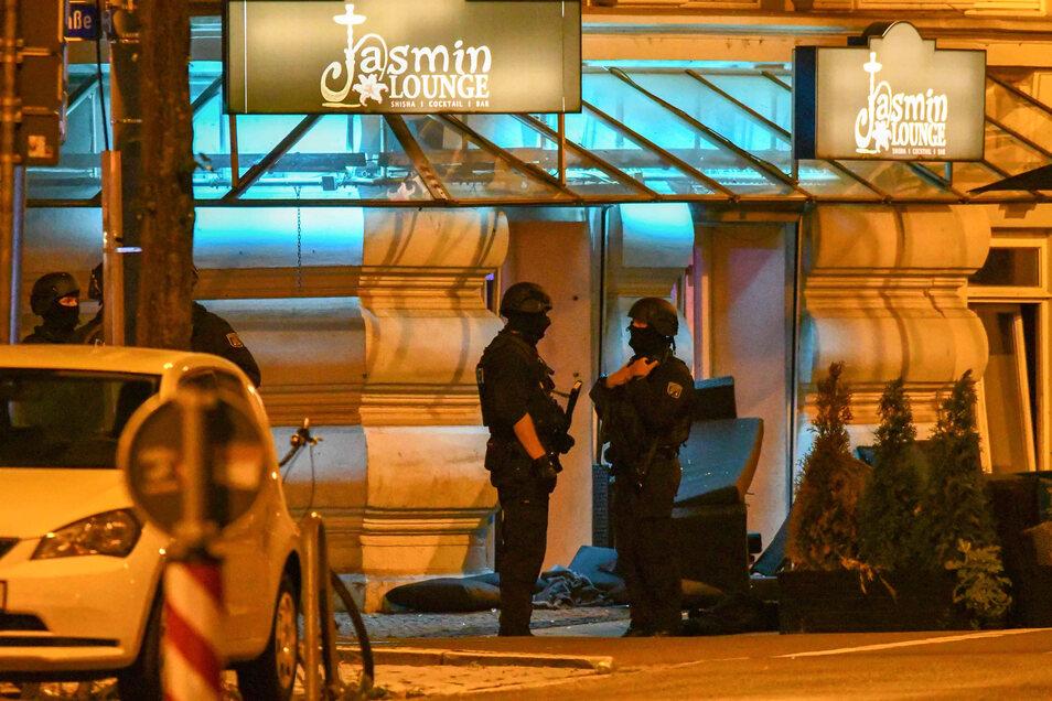 Polizisten in Schutzausrüstung stehen vor der Shisha-Bar im Magdeburger Zentrum.