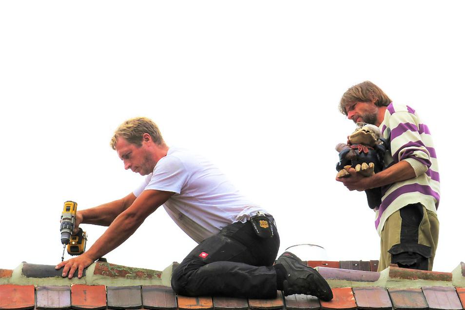 Zimmermeister Torsten Mrose (links) bohrt die Befestigung für den Bäcker-Raben (oben) auf den Giebelfirsten des neuen Backhauses der Krabatmühle in Schwarzkollm.